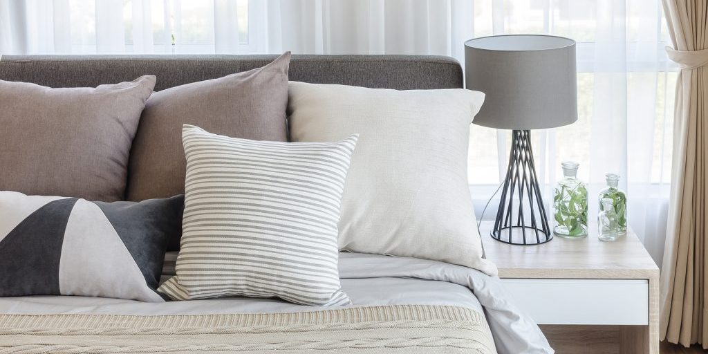 Modern Style Bedroom With Pillows On Bed And Modern Grey Lamp On